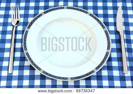 Empty Plate, Knife And Fork On The Chrckered  Picnic Tablecloth