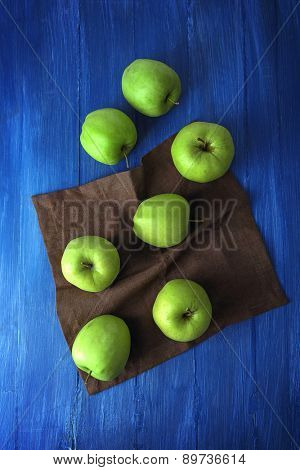 Green apples on wooden table with napkin, top view