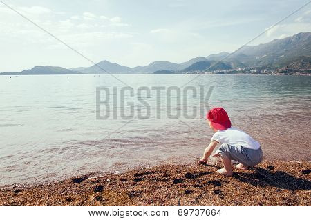 Cute boy playing and having fun on the beach.