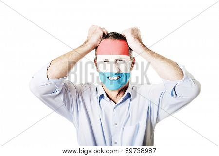 Mature man with Luksemburg flag painted on face.