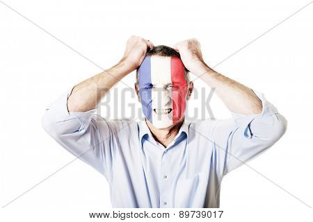 Mature man with French flag painted on face.