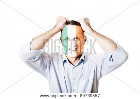 Mature man with Ireland flag painted on face.