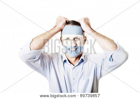 Angry mature man with Argentina flag painted on face.
