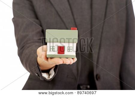 Businesswoman presenting house model in hand.