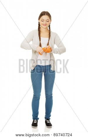 Happy teen woman squeezing a sponge.