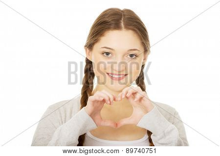 Smiling teen woman making heart shape with her hands.