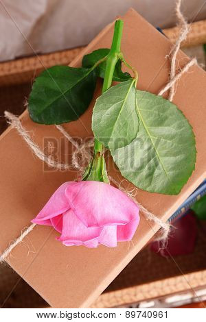 Beautiful pink roses with stack of books in suitcase, closeup