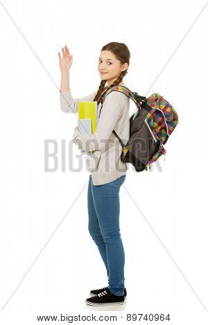 Teenager girl with school backpack waving hand.