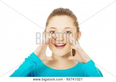 Happy teenage woman whispering a gossip.