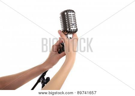 Retro microphone in female hands isolated on white