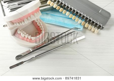 White teeth and dental instruments on table background