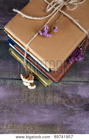 Stack of books with dry flowers on wooden background