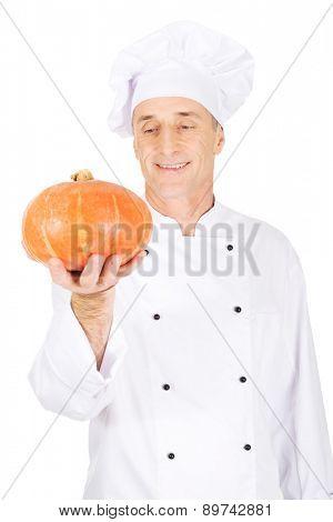 Male chef in uniform holding a pumpkin