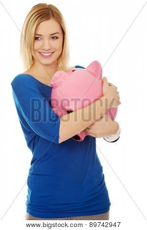 Happy casual woman with piggybank.