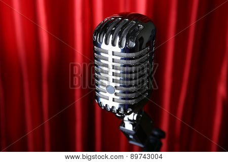 Retro silver microphone on red fabric background
