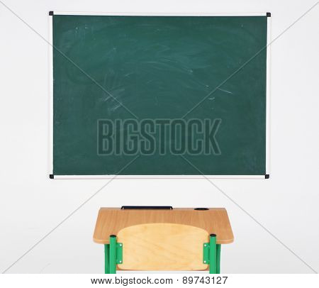 Blackboard and wooden desk with chair in class