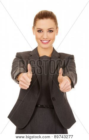 Happy business woman showing thumbs up.