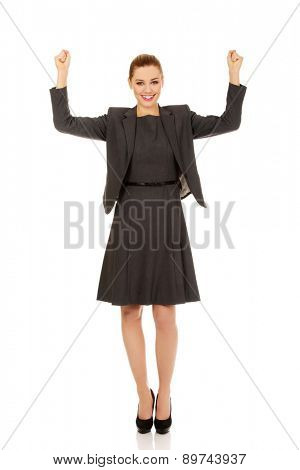 Cheerful successful businesswoman with hands up.