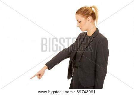 Beautiful young businesswoman pointing down.