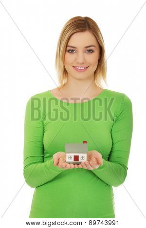 Happy woman presenting house model.