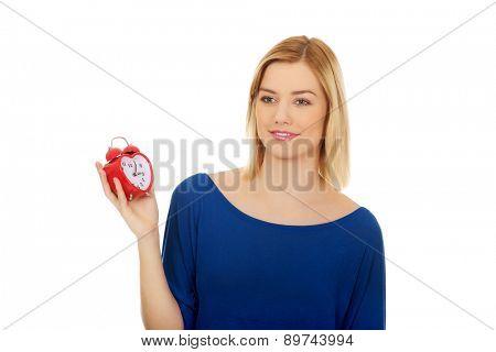 Happy woman holding an alarm clock.