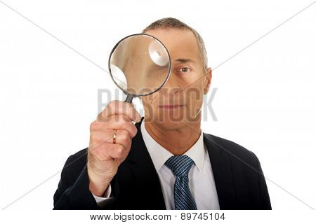 Portrait of businessman with a magnifying glass.