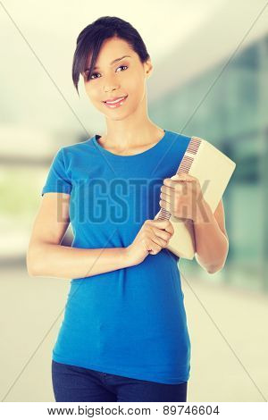 Happy young woman holding book