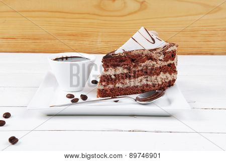 breakfast hot coffee mug and cream chocolate layer cake decorated with white chocolate slice and cream flower on white plate over wood