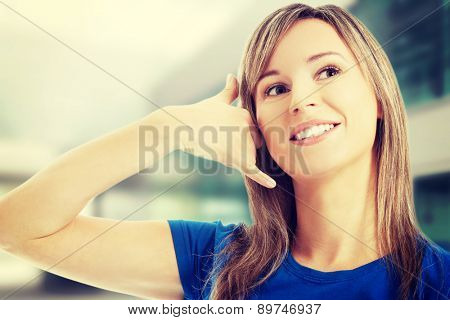 Happy woman making phone gesture