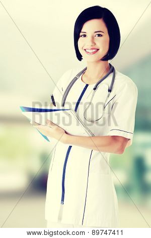 Attractive medicine student or doctor with notebook.