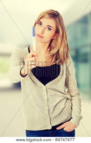 Sad young woman holding pregnancy test.