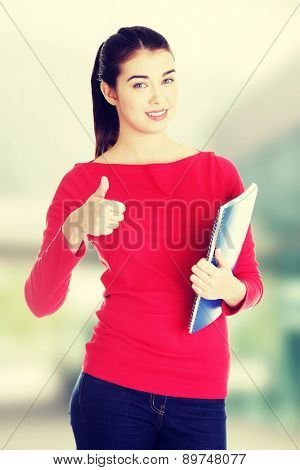 Portrait of attractive caucasian smiling woman gesturing thumb up
