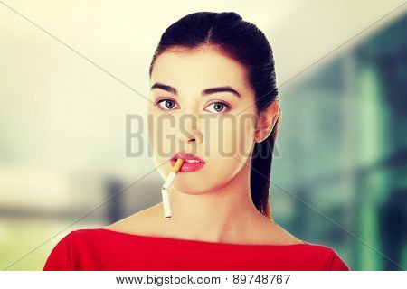 Young woman with broken cigarette