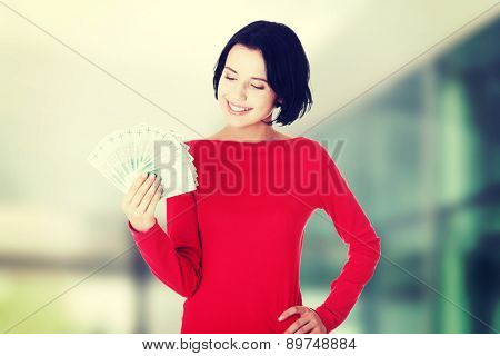 Cheerful young lady holding cash - polish zloty (pln)