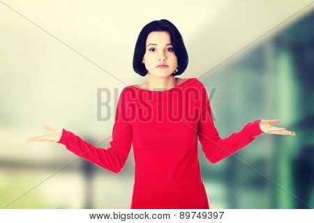 Young female gesturing do not know sign.