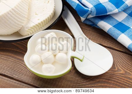Dairy products on wooden table. Mozzarella and curd cheese