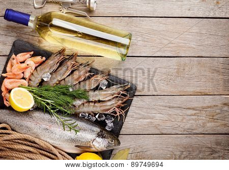 Fresh raw sea food with spices and whtie wine bottle on wooden table background. Top view with copy space