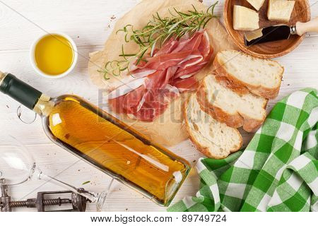 Prosciutto, wine, ciabatta, parmesan and olive oil on wooden table. Top view with copy space