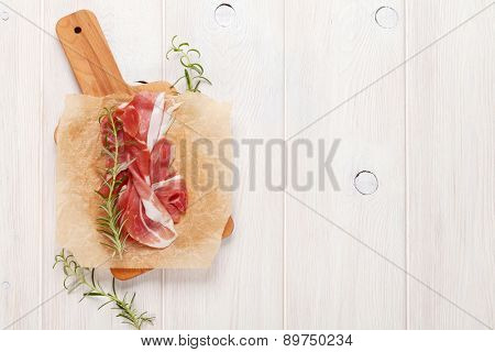 Prosciutto with rosemary on cutting board. Top view with copy space