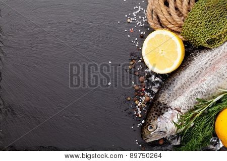 Fresh raw rainbow trout fish with spices and fishing equipment on black stone background. Top view with copy space
