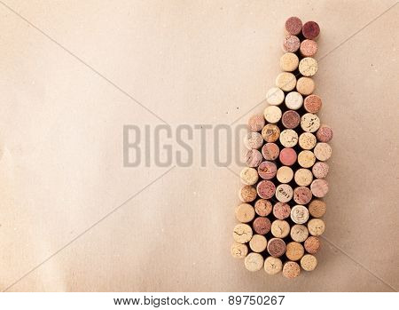 Wine bottle shaped corks over cardboard background. Top view with copy space