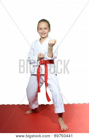 Cheerful girl stands in rack of karate