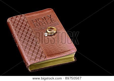 Holy Bible With Wedding Rings Isolated On Black