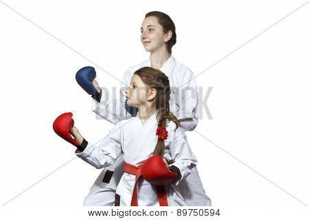 Sisters in karategi and in linings are standing in the rack karate