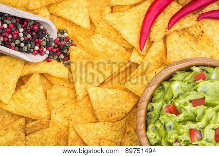 Guacamole In Wooden Bowl With Tortilla Chips And Ingredients Overhead