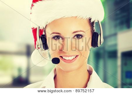 Young business woman in santa hat, microphone and headphones
