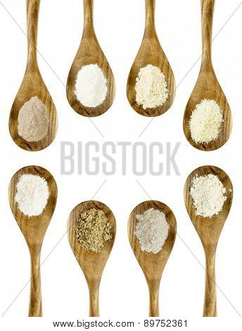 gluten free flours  set (almond, coconut, flax meal, brown rice, quinoa, teff, potato, buckwheat) - top view of isolated wooden spoons with a copy space