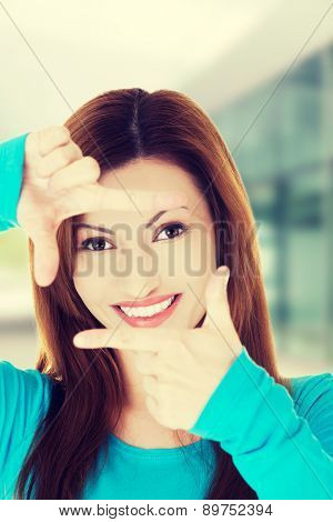Happy woman gesturing frame sign