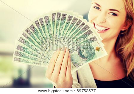 Woman holding a clip of polish money in hand