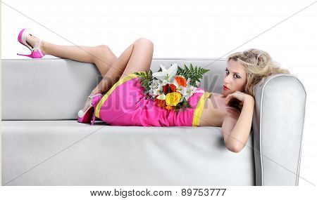 woman lying on the couch with a bouquet of flowers in hand